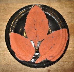 Kleiner schwarzer Teller mit Blattabdrücken